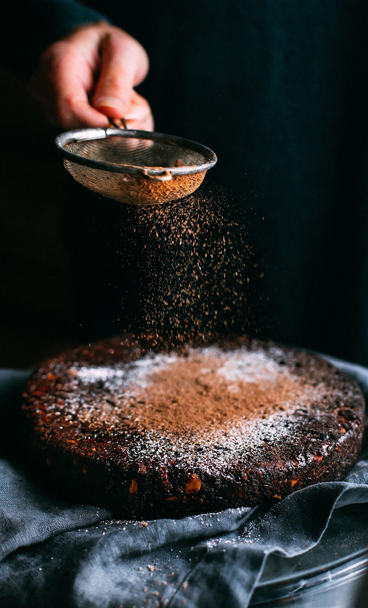 personne saupoudrant du chocolat en poudre sur un gâteau au chocolat