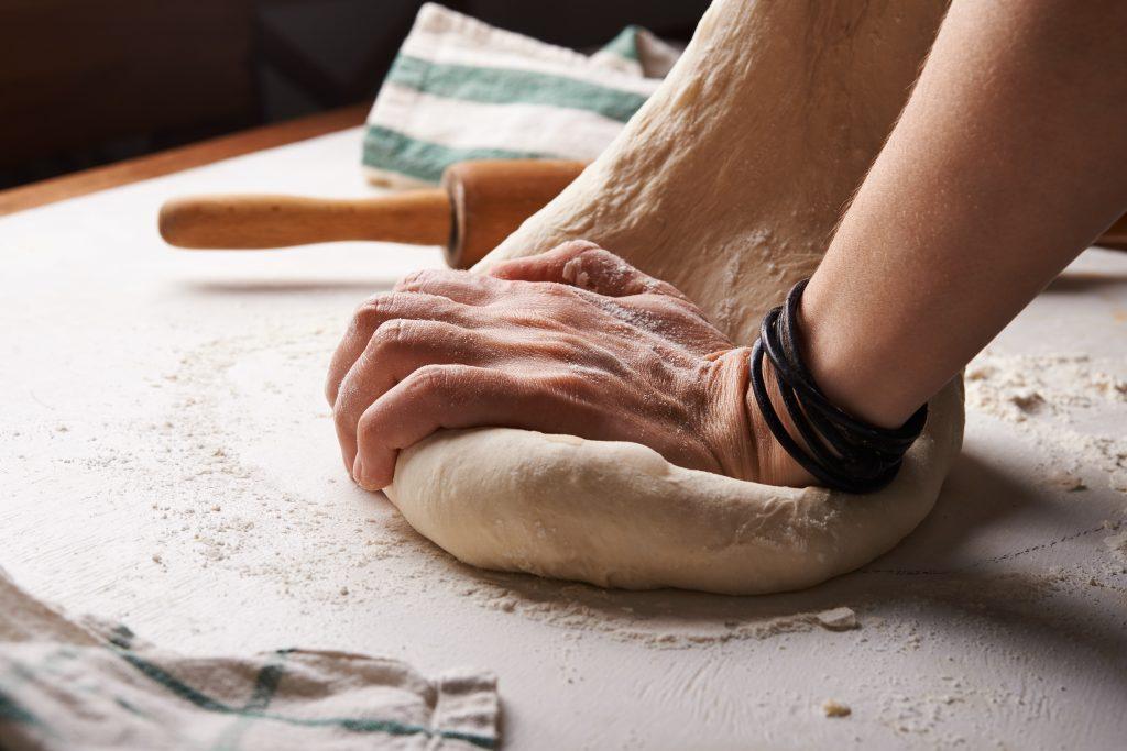 mains qui pétrissent de la pâte sur plan de travail fariné près d'un rouleau à pâtisserie